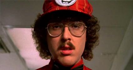 "Photo of Weird Al Yankovich dressed in a fast food uniform and looking depressed in the movie, ""UHF."""